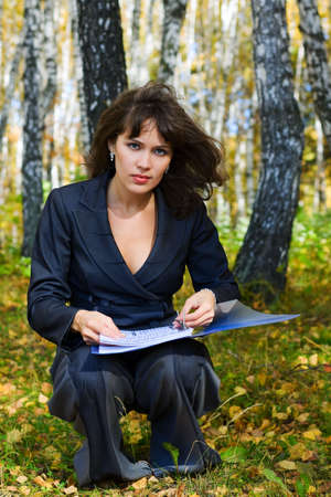 Young businesswoman with a folder on nature. photo