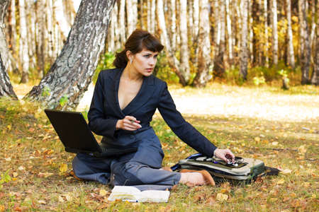 Young businesswoman using laptop on nature. photo
