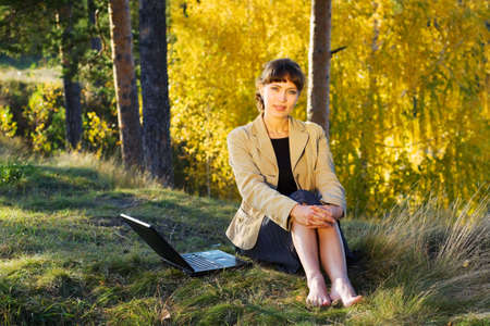 Young businesswoman using laptop on nature. Stock Photo - 6133802