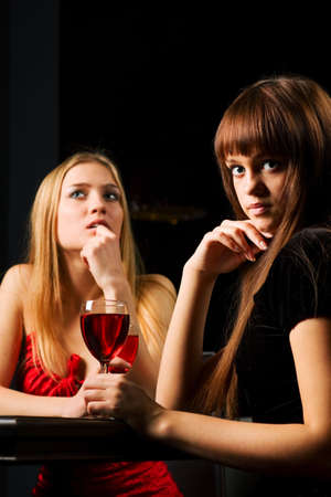 Two young women drinking red wine in a bar. Stock Photo - 6133804