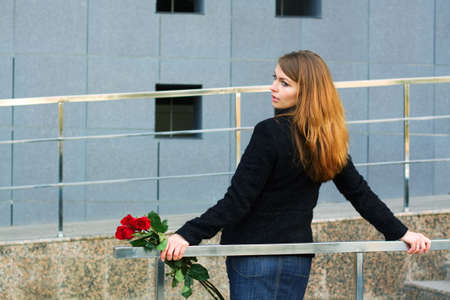 Sad woman holding a bouquet of roses. photo