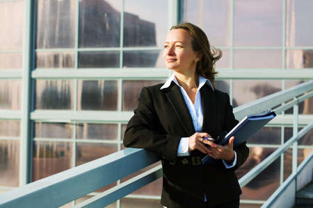 Businesswoman with a folder against industrial background. photo