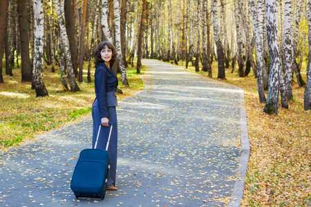 Young businesswoman with a luggage walking on the road. photo