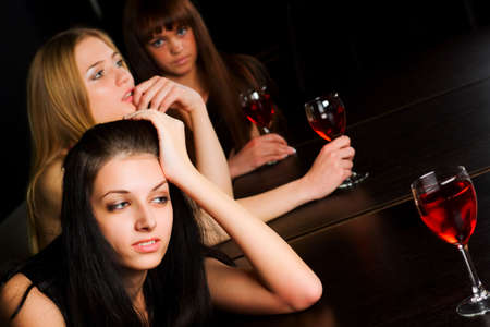 Three young women drinking red wine in a bar. Stock Photo - 6501702