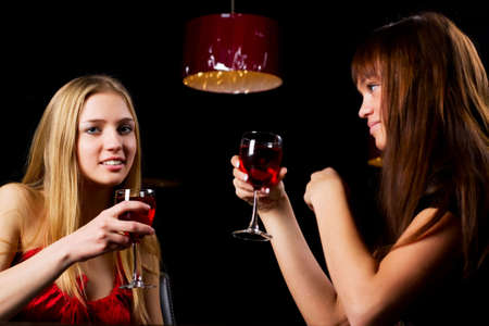 Two young women drinking red wine in a bar. Stock Photo - 6501696