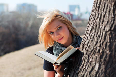 Thoughtful young woman reading a book. photo