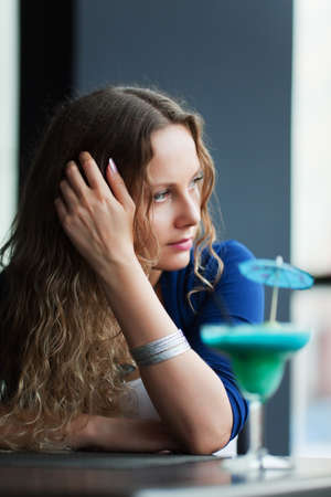 Sad young woman with a cocktail at a restaurant. Stock Photo - 7011465