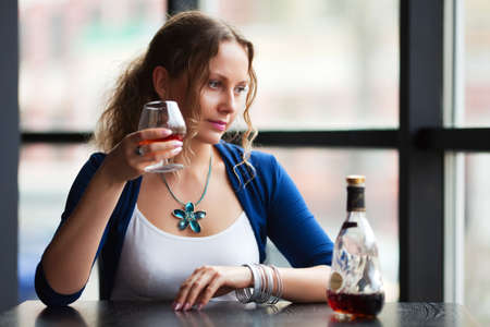 drunk girl: Beautiful young woman drinking cognac at a restaurant. Stock Photo