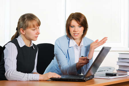 Two young businesswomen working on laptop. photo