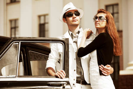 Young couple with a retro car. Stock Photo