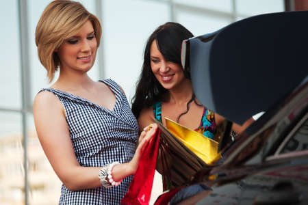 Two young women are placed shopping bags in the trunk of a car. photo