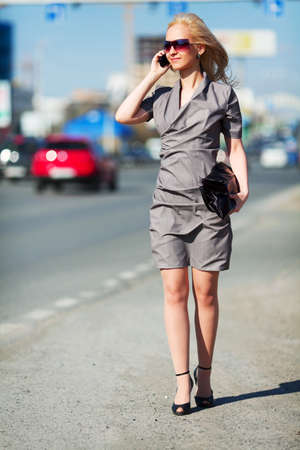Young woman on the phone walking on a city street. photo
