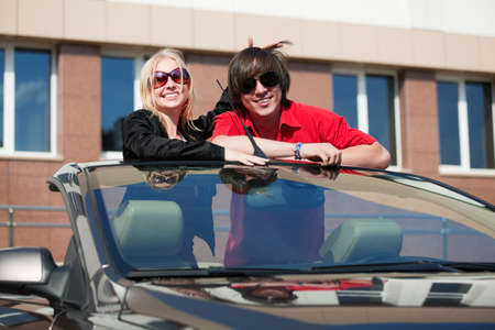 Happy young couple in the convertible car. photo