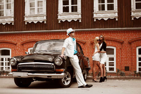 Young people with a retro car on a city street. photo