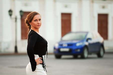 Young woman with a car on the city street. photo