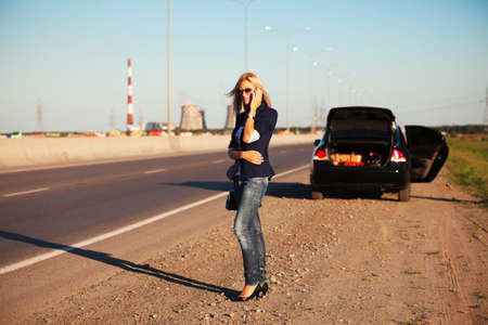 Young woman with a broken car on the road. photo