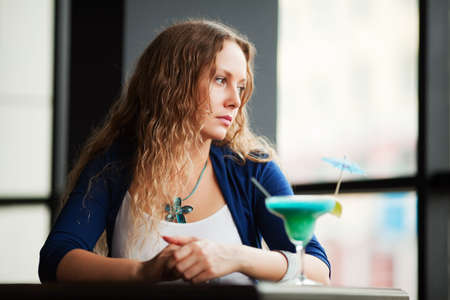 Sad young woman with cocktail in restaurant. Stock Photo - 8080364