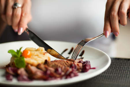 Female hands with a dinner at restaurant. Stock Photo