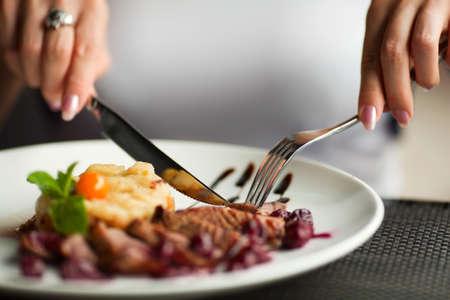 ni�a comiendo: Manos femeninas con una cena en el restaurante.