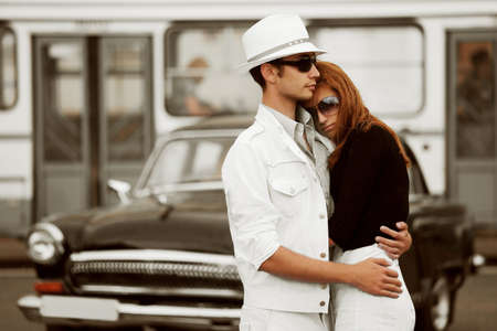 urban travel: Young couple against a retro car. Stock Photo