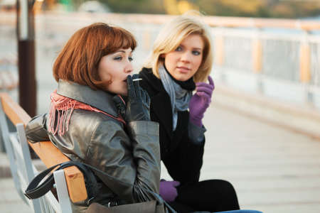 women smoking: Two young women sitting on a bench.