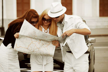 Young tourists with a road map against retro car. photo