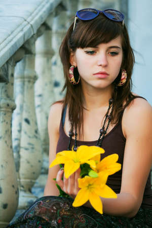 Sad young woman with a lily.