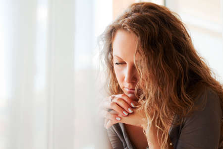 Mujer triste contra una ventana.