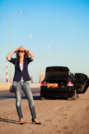 broken car: Mujer joven con un coche roto en la carretera.