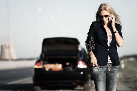 broken car: Mujer joven con un coche roto pidiendo ayuda. Foto de archivo