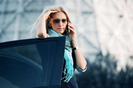 llamando: Empresaria en el tel�fono frente a un fondo industrial. Foto de archivo