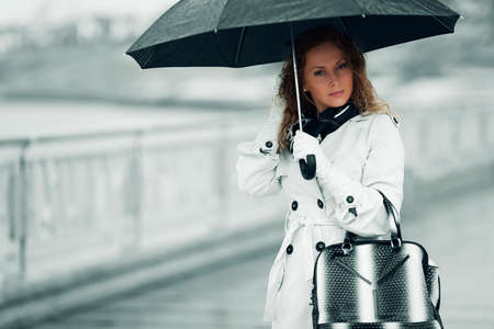Thoughtful woman with umbrella in the rain. photo