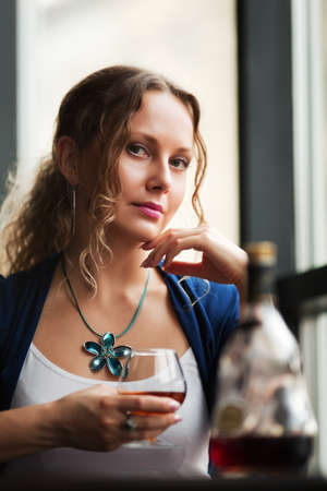 Beautiful young woman drinking cognac at a restaurant. photo
