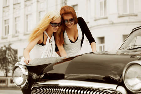 Two young women with a road map on the retro car. photo