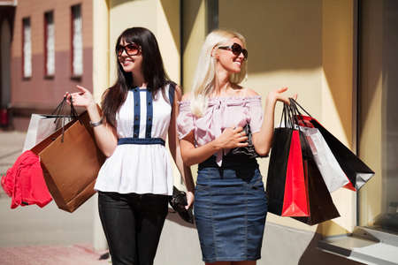 Two young women with shopping bags. Stock Photo