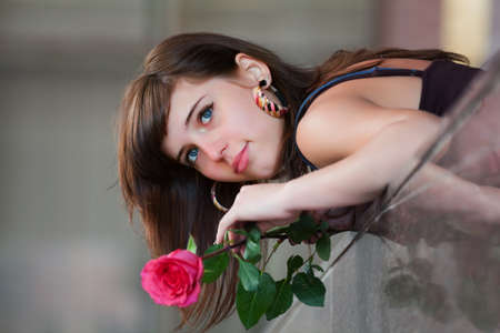 girl in love: Portrait of young woman with a red rose. Stock Photo