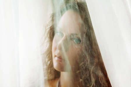 Sad beautiful woman looking through a window. photo