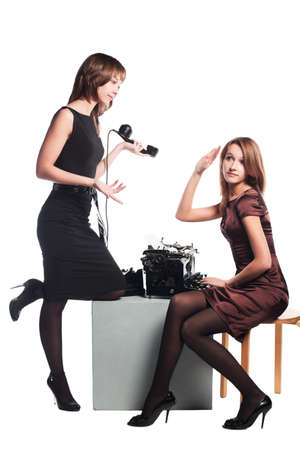 Young secretaries with a retro typewriter and old phone photo