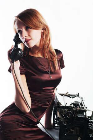 Young secretaty calling on the retro phone photo