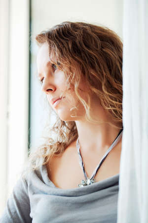 Sad woman looking out the window Stock Photo - 8861137