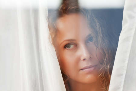 Woman looking through a window photo