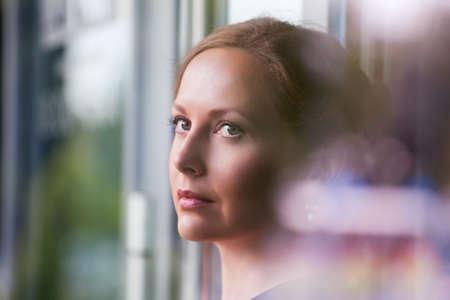 Hermosa mujer mirando a través de la ventana Foto de archivo