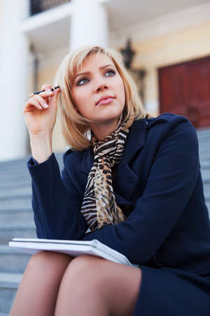 Young businesswoman with notebook on the steps photo
