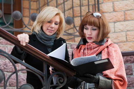 Two young businesswomen with financial reports photo