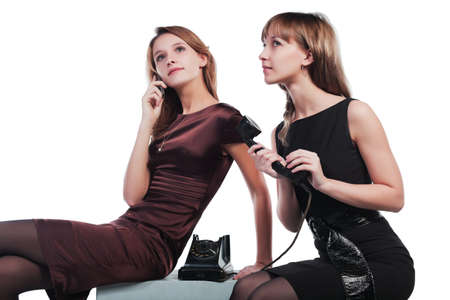 Two young women with a retro and mobile phones photo