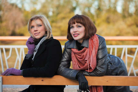 Two young women sitting on a bench photo