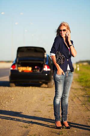 broken car: Mujer joven con un coche roto pidiendo ayuda