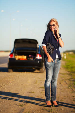 calling for help: Young woman with a broken car calling for help