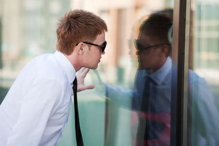Young businessman looking through a window photo