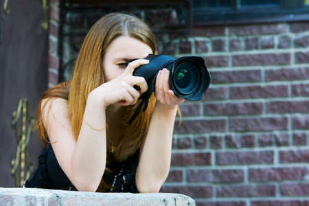 Young woman holding a digital photo camera photo